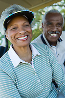Senior couple in golf course smiling (portrait)