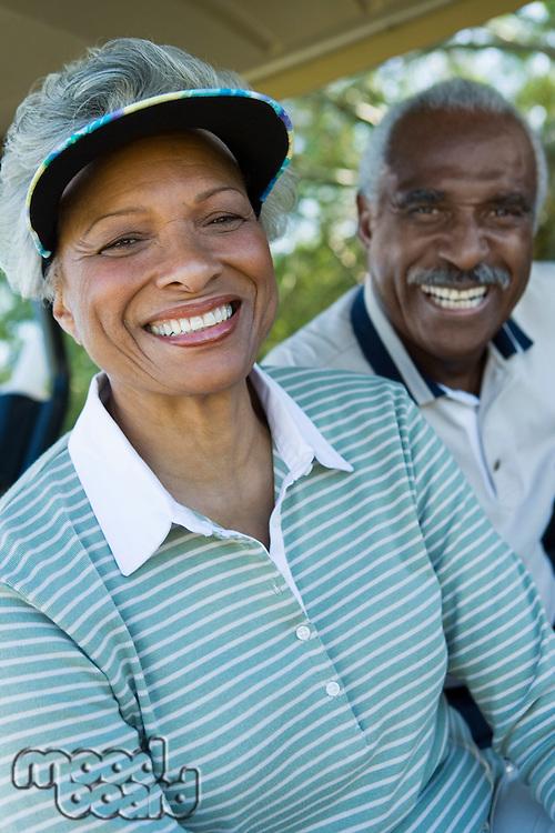 Senior couple in golf course smiling (portrait)