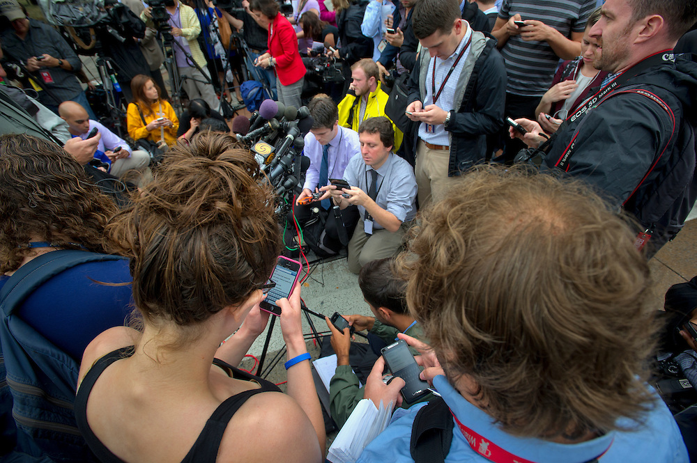 "DISTRICT OF COLUMBIA (Sept. 16, 2013) -- The national press corps report back to their bureau using smart phones during a shooting at the Washington Navy Yard in the nations capitol. 13 people including the assailant were killed at the Washington Navy Yard that started on Monday morning after the shooter fired inside the Naval Sea Systems Command Headquarters building around 8:15 a.m. A host of law enforcement agencies from the Metropolitan Police Department, the Military Police and others assisted with the response. There was a ""shelter in place"" order while law enforcement agencies entered the building to confront the shooter who was eventually killed.  Photo by Johnny Bivera"