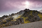 Two hikers stand near the summit of a steaming volcanic cone at Landmannalaugar, located in the highlands of Iceland. Landmannalaugar, part of the Fjallabak Nature Reserve, sits at the edge of the Laugahraun lava field, which was formed in an eruption around the year 1477.