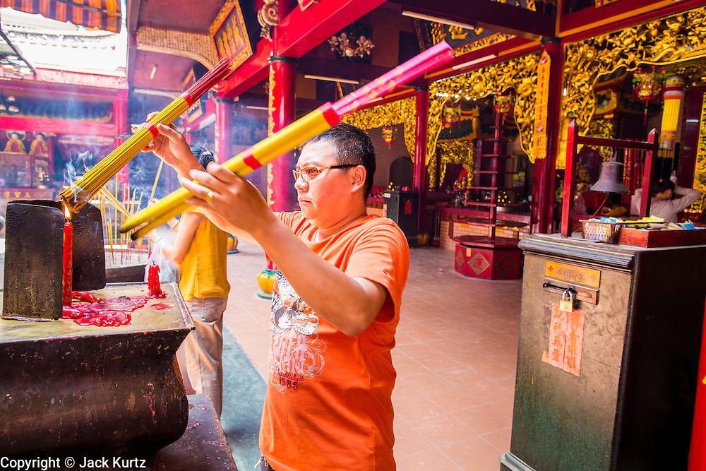 "12 APRIL 2012 - HO CHI MINH CITY, VIETNAM:   A Buddhist lights incense in Chùa Quan Âm (Avalokiteshvara Pagoda), a Chinese style Buddhist pagoda in Cho Lon. Founded in the 19th century, it is dedicated to the bodhisattva Quan Âm. The pagoda is very popular among both Vietnamese and Chinese Buddhists. Cholon is the Chinese-influenced section of Ho Chi Minh City (former Saigon). It is the largest ""Chinatown"" in Vietnam. Cholon consists of the western half of District 5 as well as several adjoining neighborhoods in District 6. The Vietnamese name Cholon literally means ""big"" (lon) ""market"" (cho). Incorporated in 1879 as a city 11 km from central Saigon. By the 1930s, it had expanded to the city limit of Saigon. On April 27, 1931, French colonial authorities merged the two cities to form Saigon-Cholon. In 1956, ""Cholon"" was dropped from the name and the city became known as Saigon. During the Vietnam War (called the American War by the Vietnamese), soldiers and deserters from the United States Army maintained a thriving black market in Cholon, trading in various American and especially U.S Army-issue items.          PHOTO BY JACK KURTZ"