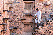 TAGADIRT, MOROCCO - MAY 26TH 2016 - A local climbs the stone steps at the Tagadirt Granary (Agadir Tagadirt), Ighrem and Tafraoute province of the Souss Massa Draa, Southern Morocco.