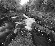 The picturesque Southbranch Falls and fall colors rendered in monochrome, Baxter State Park, Maine, USA