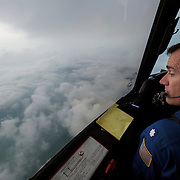 "Cmdr. Carl Newman looks out of window into the eye of Hurricane Irene as he flies a P-3 Orion turboprop named ""Kermit"" over the Atlantic Ocean Tuesday, Aug. 23, 2011. Congress is looking to slash funds wherever possible; the MacDill-based hurricane hunter program is on the chopping block. NOAA will make several flights into the eye of hurricane Irene in the coming days in order to predict where the storm is headed and its intensity."