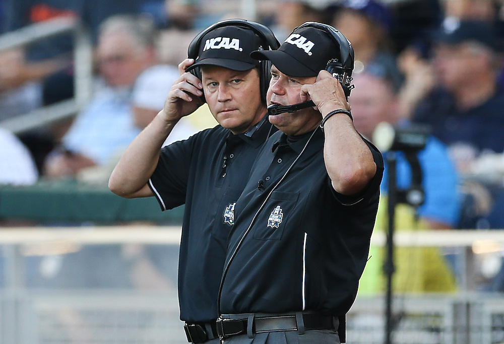 OMAHA, NEB.  -- 06/19/2016:   Field umpires consult with review officials as they review a hit to deep right field by Coastal Carolina's Zach Remillard (7) against Florida in the top of the third inning during game four of the College World Series at TD Ameritrade Park in Omaha, Neb., Sunday, June 19, 2016.  The play was reviewed and reversed following the first video reviewed play in CWS history.<br /> MATT DIXON/THE WORLD-HERALD