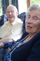 A couple of older people relaxing in the communal lounge of a residential nursing home,