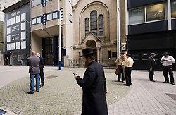 Pedestrians and diamond dealers make their way past a synagogue on Hoveniersstraat in the heart of the diamond district in Antwerp, Belgium, on Wednesday August 26, 2009. (Photo © Jock Fistick)