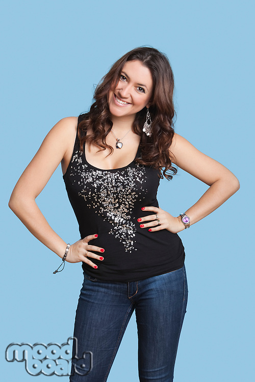 Portrait of beautiful woman with hands on hips smiling over blue background