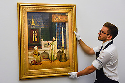 "© Licensed to London News Pictures. 11/10/2019. LONDON, UK. A technician presents ""Koranic Instruction"", 1890, by Osman Hamdy Bey, (Est GBP3-6m).  Preview of works from the Najd Collection of orientalist paintings at Sotheby's in New Bond Street, which record daily life in the historic Arab, Ottoman and Islamic worlds  All 155 paintings are on public view 11- 15 October, with 40 works to be auctioned on 22 October.  Photo credit: Stephen Chung/LNP"