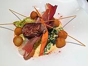 Vienna, Austria. Restaurant Five Senses.<br /> Main course.<br /> Medaillons vom Jungschweinfilet | cremiger Trüffelkohl | Speckstaub | Pommes Noisette<br /> Medaillons of young pork fillet | creamy truffle cabbage | bacon powder | nut potatoes