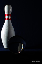 bowling pin on a dark background reflected in the foreground by a 105mm glass sphere
