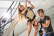 """Here being harnessed in in preparation - Performance Artist Millie Brown performs """"Rainbow Body""""- a site specific performance installation, where she suspends her body surrounded by crystal prisms, from the ceiling of the gallery on Dover Street for the duration of Frieze one of the busiest weeks in the captial's art scene. Contemporary art gallery Gazelli Art House supports and presents a wide range of international artists."""