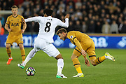 Christian Eriksen of Tottenham Hotspur is tackled by Leroy Fer of Swansea City during the Premier League match between Swansea City and Tottenham Hotspur at the Liberty Stadium, Swansea, Wales on 5 April 2017. Photo by Andrew Lewis.