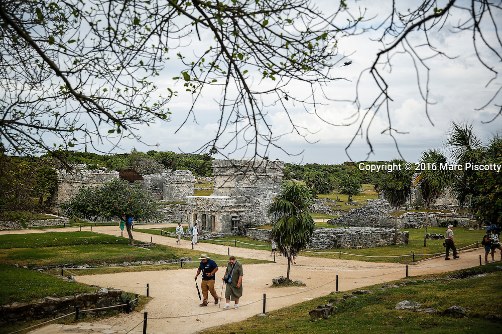 SHOT 12/10/16 8:24:11 AM - Tourists walk the grounds of Tulum. Tulum is the site of a pre-Columbian Mayan walled city serving as a major port for Cobá. The ruins are situated on 12-meter (39 ft) tall cliffs, along the east coast of the Yucatán Peninsula on the Caribbean Sea in the state of Quintana Roo, Mexico. Tulum was one of the last cities built and inhabited by the Maya; it was at its height between the 13th and 15th centuries and managed to survive about 70 years after the Spanish began occupying Mexico. Old World diseases brought by the Spanish settlers appear to have resulted in very high fatalities, disrupting the society and eventually causing the city to be abandoned. One of the best-preserved coastal Maya sites, Tulum is today a popular site for tourists. Tulum is located in the Mayan Riviera and along the east coast of the Yucatán Peninsula on the Caribbean Sea in the state of Quintana Roo, Mexico. (Photo by Marc Piscotty / © 2016)