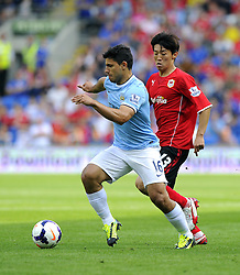 Manchester City's Sergio Aguero drives the ball past Cardiff City's Kim Bo-Kyung  - Photo mandatory by-line: Joe Meredith/JMP - Tel: Mobile: 07966 386802 25/08/2013 - SPORT - FOOTBALL - Cardiff City Stadium - Cardiff -  Cardiff City V Manchester City - Barclays Premier League