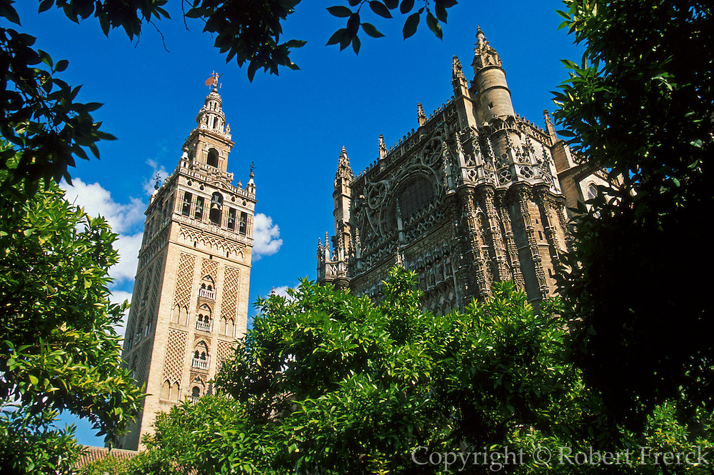 SPAIN, ANDALUCIA, SEVILLE the Cathedral facade and the Giralda belltower (originally Moorish minaret) seen from the Patio of the Oranges