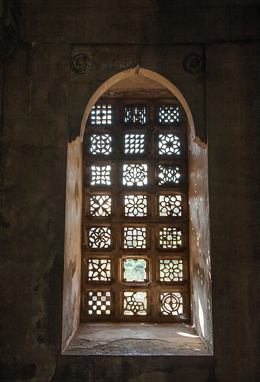 View from the interior of the window of pierced stone in squares, each square filled with a geometric or curvelinear motif.