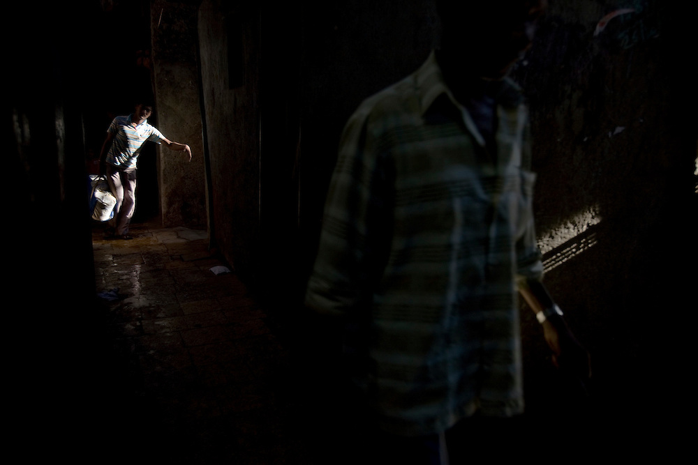 """A labourer walks through the dark alleys, in the Daharavi slum area in Mumbai, India, on Feb. 4, 2009.A sprawling slum area in the heart of the fastest growing city in the world, Dharavi and its affiliate slum areas have been thrust into limelight in the year 2008 like never before. Earlier it was the slum redevelopment authorities who threatened to break down the shanties and build new infrastructural projects, and during the far end of the year it was the movie """"Slum Dog Millionaire"""". Winning Gloden Globes, 8 Oscar's & 7 Bafta's the movie has bought to light the ruggedness and the struggle of the life in the slums of Indian cities. While the movie is a fairy tale story of positive endings the real hardship, unemployment and economic disparities seen in the slums is striking and deplorable. Yet the slums of Mumbai offer hope and oppurtunity to the few who travel and live away from their native villages and try make a living out of India's growth curve and rapid industrial progress. .. 2009 brings with it, recession, downturn and unemployment. In this scenario the life in the slum gets more rugged and difficult. This photo essay is a peek into the daily lives of city slum dwellers who live, hope, dream, relax, enjoy in the premises of these slums at the fringes of progress and development awaiting for an oppurtunity to break free into the other side."""