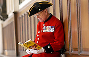 Chelsea Pensioner Alan Gale at the Royal Hospital Chelsea in uniform with his military medals reading a book on wood carving, his great hobby.