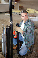 Mature man looking away while holding pipe and drill
