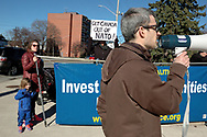 CANADA, Windsor. 07 April 2017. Windsor Peace Coalition holds a demonstration against yesterday's United States bombing of a Syrian air force base. About twenty people, mostly older, gather at Jackson Park during the afternoon rush hour. There is also a counter demonstration by two men holding a Trump banner on the same street corner.