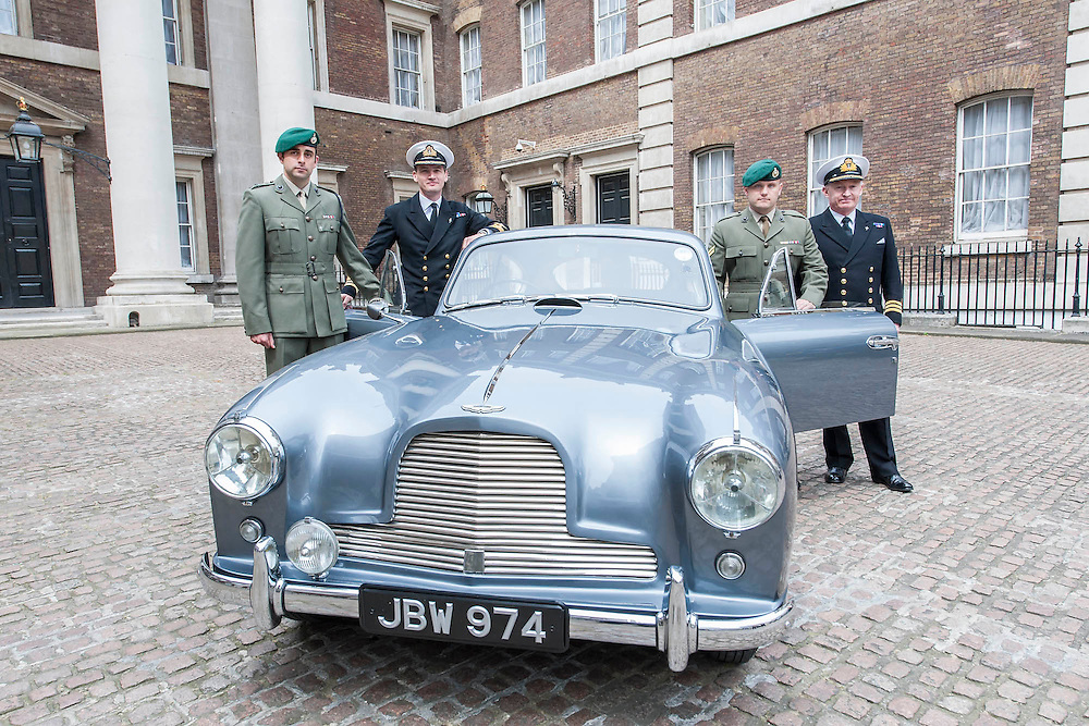 Captain Tom Mobbs RM , Commander Paul Haines RN, Corporal James, Martin RM and Commander Pat Douglas RN (l to r) stand with the car.An Aston Martin DB 2/4, which is understood to have been Ian Fleming's inspiration for James Bond's Aston Martin in the original novel Goldfinger. It was recently discovered and refurbished by owners  John and Daniel Walford.  It is to be auctioned on 12 July at Blenheim Palace  by international auctioneers Coys. The Old Admiralty Building, Whitehall London