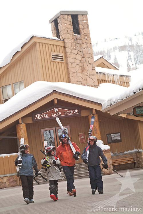 family walking with skiis in Silver Lake Village in Deer Valley Resort