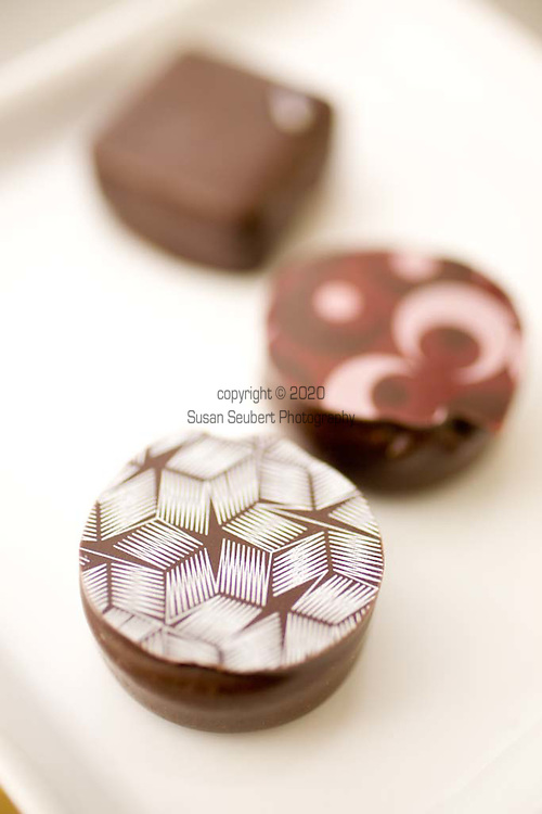"""Truffles by Ivy Chan's Cocoa Chai Chocolates.  """"Horlicks"""" with white top is malt infused into dark chocolate granache.  """"Honey Lavender"""" truffle (square) is infused into dark chocolate granache, and """"Veuve Clicquot"""" truffle (round with moons) is champagne infused dark chocolate granache."""