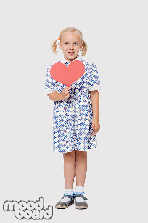 Portrait of a happy little girl holding pink paper heart over white background