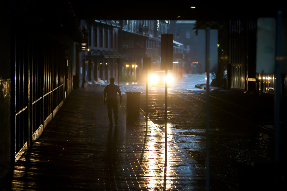 A hotel security guard walks through a tunnel on Historic River Street checking doors, Monday, Sept., 11, 2017, in Savannah, Ga., as Hurricane Irma starts to impact the area.  (AP Photo/Stephen B. Morton)