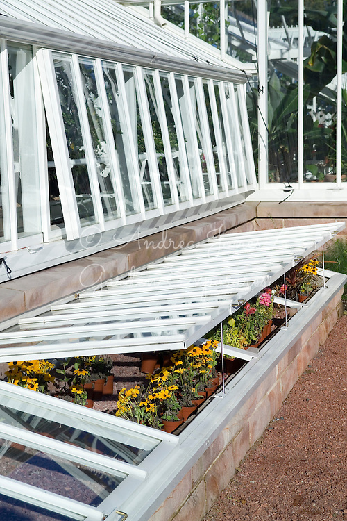Exterior of the Alitex glasshouse showing windows open, cold frames slightly raised with perennials in pots. Stonework walls with gravel hardstanding.<br /> The Spa in the Walled Garden @ Loch Lomond Golf Club<br /> Glasshouse supplied by <br /> Alitex<br /> Torberry Farm<br /> South Harting<br /> Petersfield<br /> Hampshire<br /> GU31 5RG<br /> tel&nbsp; +44(0)1730 826900<br /> www.alitex.co.uk