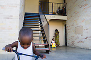 A man sits on his porch with his son hours after having their government issued Ebola quarantine lifted while Estella Ndayikunda sweeps outside her apartment with her son Fledson, 2, and Frank, 3, in Dallas, Texas on October 5, 2014.