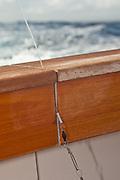 Monofilament leader and swivel stuck in gap of transom tuna door.