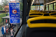 Empty top deck of  London bus stopped at a bus stop with a congestion information sign.
