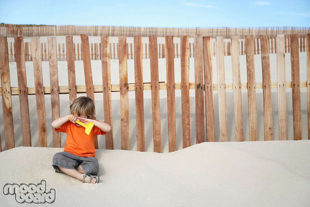 Boy (3-4) covering eyes sitting against wooden fence on sand dune