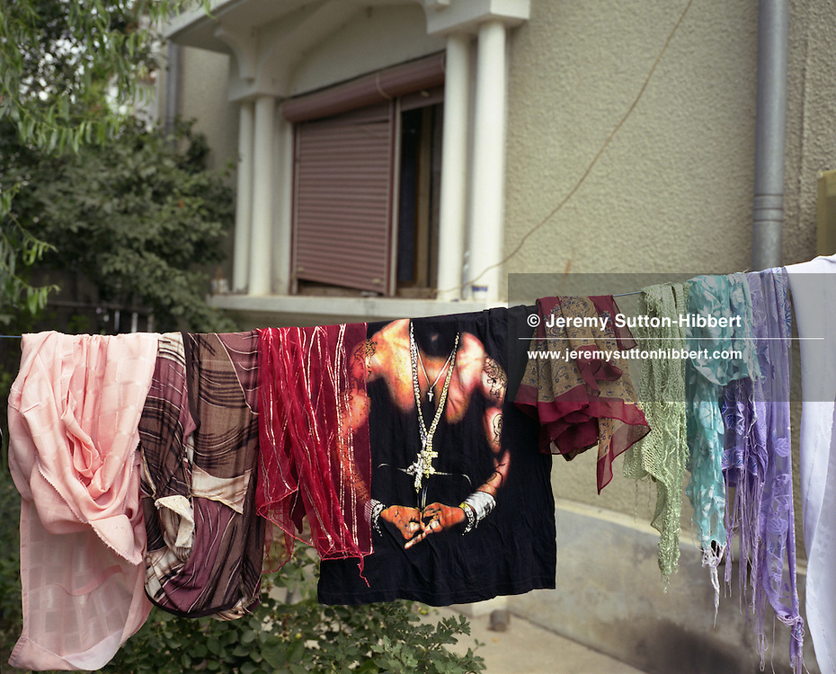 A t-shirt bearing the image of American gangster rap-musician '50 Cent' hangs beside traditional roma headscarves, in a garden in the village of Sintesti, in Romania, early August 2006. The Kalderari roma of Sintesti are by tradition metal workers, originally making alcohol stills, pots and pans, but now dealing in scrap metal. The large profits from their business have enabled them to build large houses in the village of Sintesti, 20km from Bucharest, and to invest in fast, Western brand name cars such as BMW's, Mercedes and Porsche.