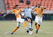 Jun 29, 2016; Houston, TX, USA; Houston Dynamo midfielder Leonel Miranda (33) and midfielder Collen Warner (26) fight for the ball against Sporting Kansas City midfielder Benny Feilhaber (10) in the second half at BBVA Compass Stadium. Dynamo won 3 to 1. Mandatory Credit: Thomas B. Shea-USA TODAY Sports