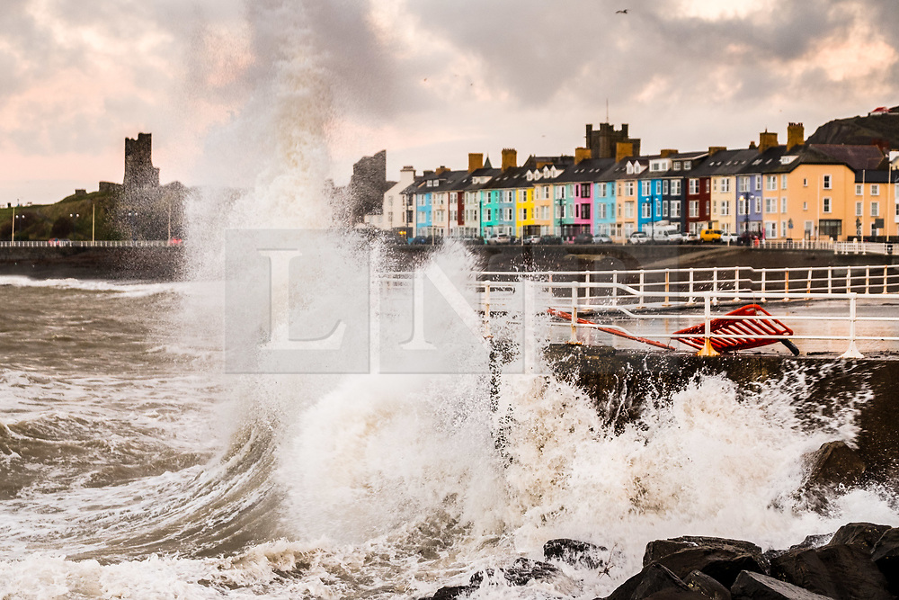 © Licensed to London News Pictures. 22/12/2018. Aberystwyth, UK. Winds and a high tide at first light combine to hammer huge waves against the sea defences in Aberystwyth on the Cardigan Bay coast of west Wales on a bright and blustery day, with more unsettled weather forecast for later in the weekend. Photo credit: Keith Morris/LNP