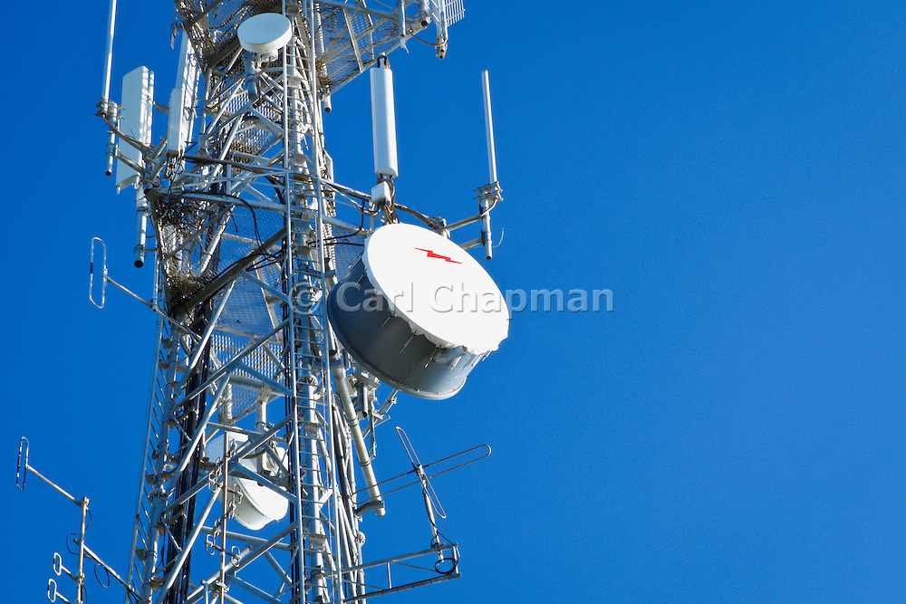 Microwave dish antenna on telecom communications tower for the cellular telephone system.
