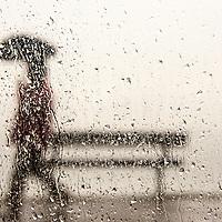 A man walking with an umbrella against a rain streaked window