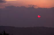 A hazy red sun rises over the Mountains of Moab behind the village of Abu Dis on the eastern outskirts of Jerusalem. WATERMARKS WILL NOT APPEAR ON PRINTS OR LICENSED IMAGES.