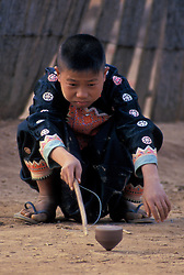 Asia, Thailand, Northern Thailand, near Mae Hong Son, Boy of Meo (Hmong) hill tribe plays with spinning wood top in village of Na Pa Paek
