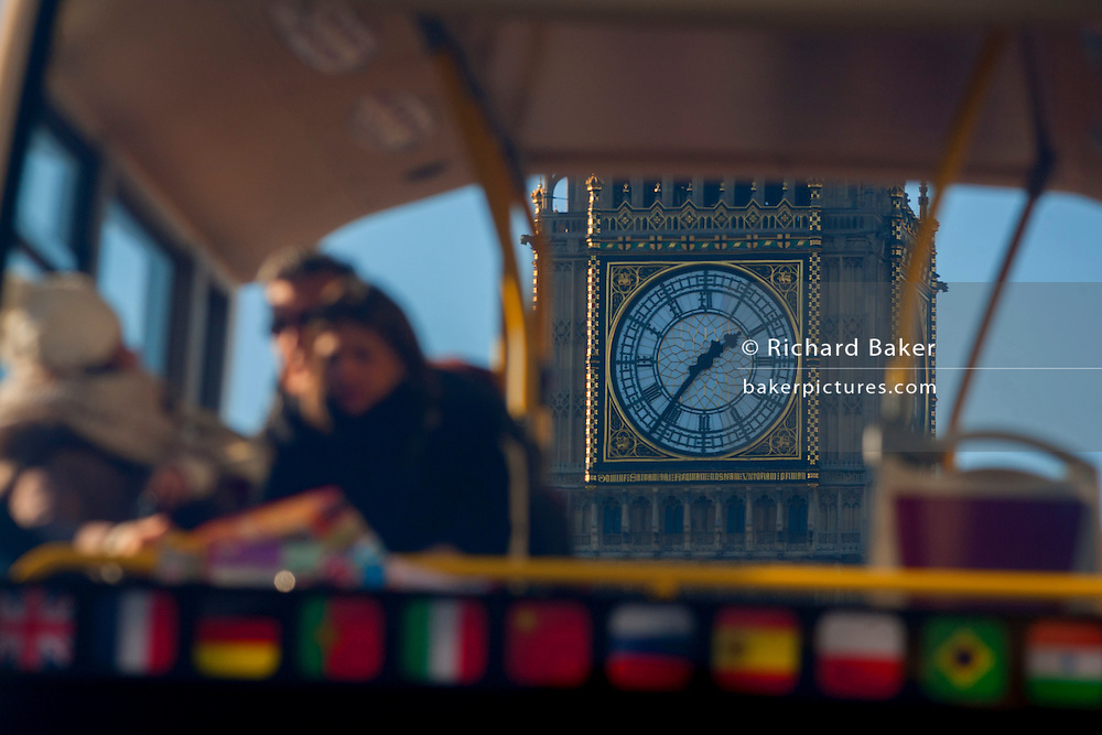A foreshortened perspective of a tour bus with tourists reading their London map and in the background, the clockface of Elizabeth Tower of the British parliament, on 17th January 2017, in London England.
