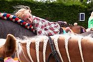 Europa, Niederlande, Zeeland, Walcheren, Ringreiten in Oostkapelle, beim Ringreiten muss der Reiter einen kleinen Ring im Galopp mit einer Lanze treffen und aufspiessen, das Turnier findet in mehreren Durchlaeufen statt, wobei der Ring immer kleiner wird, Maedchen liegt auf Pferderuecken mit geflochtener und geschmueckter Maehne.<br /> <br /> Europe, Netherlands, Zeeland, Walcheren, ring riding in Oostkapelle, the rider must impale a small ring with a lance while galloping, the tournament takes place in several runs, in which the ring becomes smaller and smaller, girl lies on horseback, braided mane.