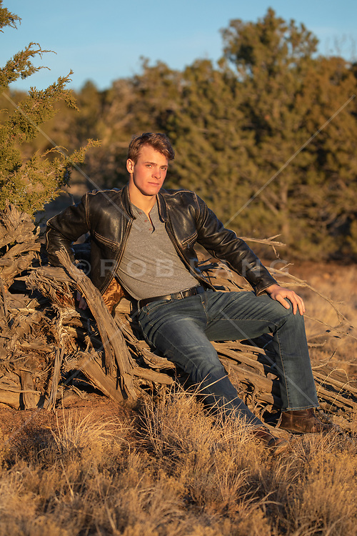 man in a leather jacket sitting in a wooded area