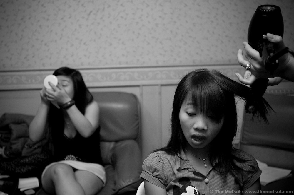 Doi, a transgendered woman, does the makeup for 12 girls of in section eight of the Violin Karaoke Bar in Chiang Mai, Thailand. Doi's day job is as staff at M Plus, an NGO providing a health clinic for sexually transmitted infections and a community center for gay, transgendered, and male sex workeres. In the evenings Doi's responsibility is the makeup for the girls of section eight for which she earns 1000 Baht per person per month; at about 12,000 Baht ($370 USD) this job nets her double the average Thai salary. From 7-9pm young women, ages 15 to 22, prepare for a night of work. Their job is to sell drinks to customers who book the karaoke rooms; in the neighboring dance club, also part of the Violin, there are cocktail waitresses. However, many are also freelance sex workers or 'bar girls' who make their own arrangements with the customers for a 'date.' Most of the customers are asian; they are either Thai, Korean, Chinese, or Japanese.