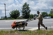 """DACULA, GA – JUNE 6, 2014: Karl Bushby travels along Highway 124, several miles east of Atlanta, Georgia. Bushy walks about 20 miles a day, and has admitted that his quest to get permission to travel through Russia is a long shot. """"If I skip Russia and just start walking through China, I've failed.""""<br /> <br /> Karl Bushby is trying to complete the longest walk in history. Unless the Russians stop him. As a 45 year-old Brit, Bushby been traveling around the world on foot since 1998. In the most recent leg of his journey, Bushby is walking to Washington, D.C. to petition the Russian Embassy to lift a visa ban that prohibited him from continuing his hike through Russia."""