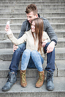 Full length of young couple taking picture of themselves while sitting on steps outdoors