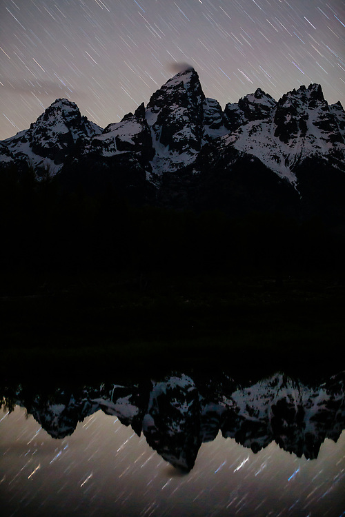 Stars are reflected in still waters after dark in the Tetons.