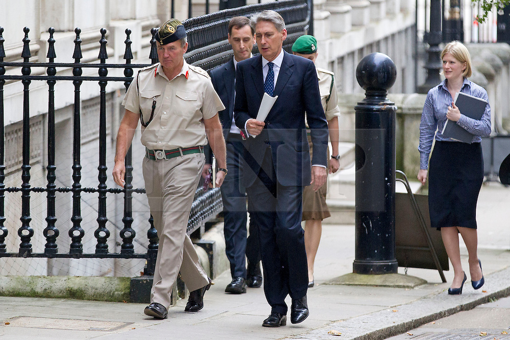 © Licensed to London News Pictures. 23/09/2013. London, UK. On the day of an emergency meeting of the COBRA committee to discuss the recent Kenyan terrorist attack Philip Hammond, the British Defence Secretary, is seen on Downing Street today (23/09/2013) with a British Army General. Photo credit: Matt Cetti-Roberts/LNP